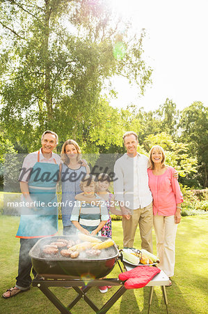 Multi-generation family standing at barbecue in backyard Stock Photo - Premium Royalty-Free, Image code: 6113-07242400
