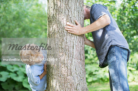 Father and son peeking around tree Stock Photo - Premium Royalty-Free, Image code: 6113-07242409