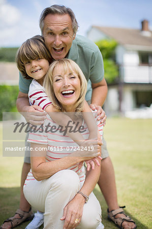 Grandparents and grandson hugging outdoors Stock Photo - Premium Royalty-Free, Image code: 6113-07242419
