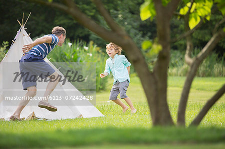 Father chasing son around teepee in backyard Stock Photo - Premium Royalty-Free, Image code: 6113-07242428