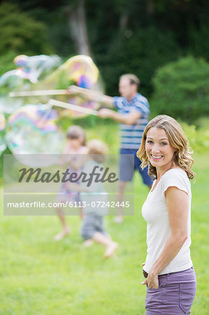 Family playing with bubbles in backyard Stock Photo - Premium Royalty-Free, Image code: 6113-07242445