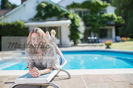 Woman laying on diving board at poolside Stock Photo - Premium Royalty-Free, Image code: 6113-07242482