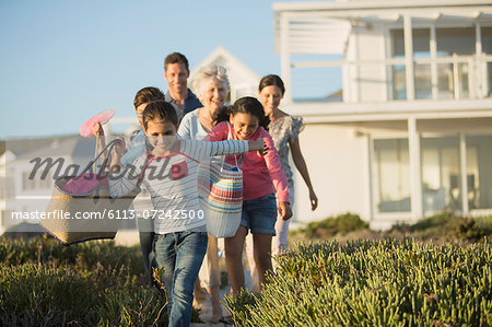 Family walking on beach path outside house