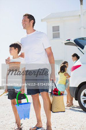 Father and son holding beach gear by car Stock Photo - Premium Royalty-Free, Image code: 6113-07242502