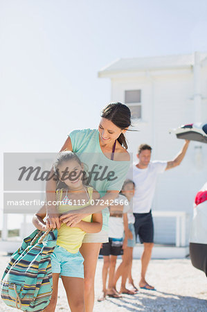 Mother and daughter hugging in sunny driveway Stock Photo - Premium Royalty-Free, Image code: 6113-07242566