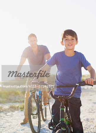Father and son riding bicycles on sunny beach Stock Photo - Premium Royalty-Free, Image code: 6113-07242572
