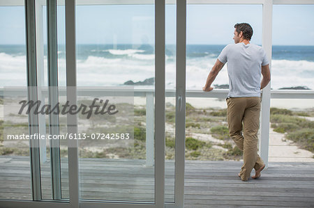 Man looking at ocean view from deck Stock Photo - Premium Royalty-Free, Image code: 6113-07242583