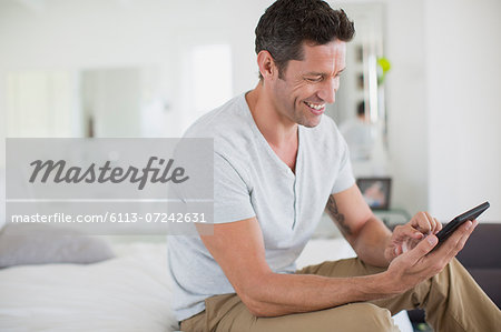 Man using digital tablet on bed Stock Photo - Premium Royalty-Free, Image code: 6113-07242631