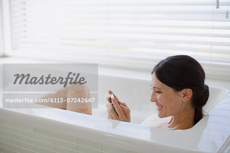 Woman using cell phone in bubble bath Stock Photo - Premium Royalty-Free, Image code: 6113-07242647
