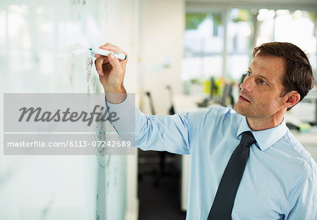 Businessman writing on whiteboard in office Stock Photo - Premium Royalty-Free, Image code: 6113-07242689