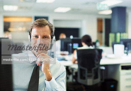 Businessman wearing headset in office Stock Photo - Premium Royalty-Free, Image code: 6113-07242742