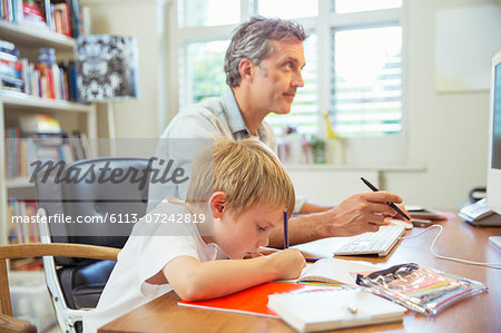 Father and son working in home office Stock Photo - Premium Royalty-Free, Image code: 6113-07242819
