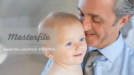 Smiling father holding baby Stock Photo - Premium Royalty-Free, Image code: 6113-07242835