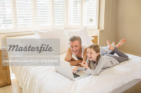 Father and daughter using laptop on bed Stock Photo - Premium Royalty-Free, Image code: 6113-07242845