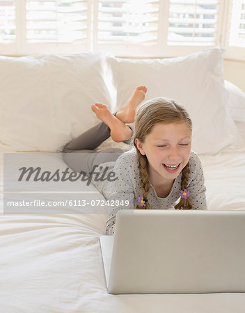 Girl using laptop on bed Stock Photo - Premium Royalty-Free, Image code: 6113-07242849
