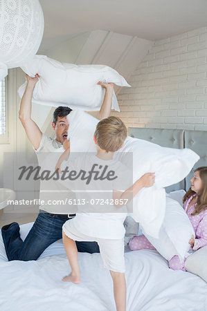 Father and children having pillow fight Stock Photo - Premium Royalty-Free, Image code: 6113-07242857