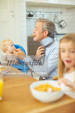 Father and children eating breakfast in kitchen Stock Photo - Premium Royalty-Free, Image code: 6113-07242893