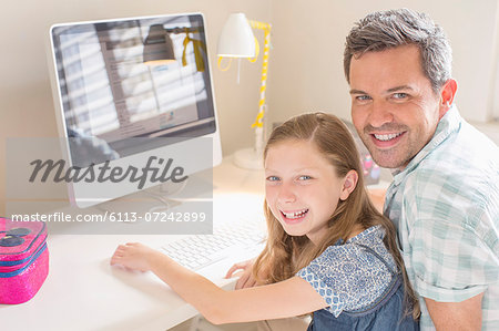 Father and daughter using computer together Stock Photo - Premium Royalty-Free, Image code: 6113-07242899