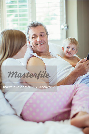 Father and children relaxing on bed Stock Photo - Premium Royalty-Free, Image code: 6113-07242917