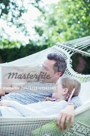 Father and children relaxing in hammock Stock Photo - Premium Royalty-Free, Image code: 6113-07242943