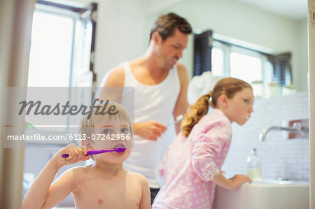 Father and children brushing teeth in bathroom Stock Photo - Premium Royalty-Free, Image code: 6113-07242956