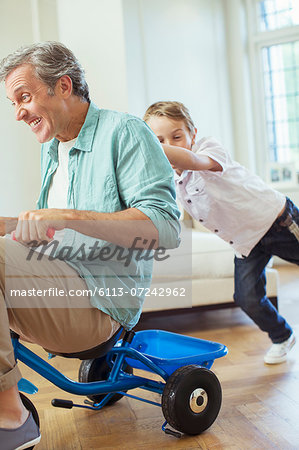 Boy pushing father on tricycle indoors Stock Photo - Premium Royalty-Free, Image code: 6113-07242962
