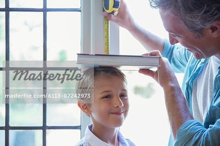 Father measuring son's height on wall Stock Photo - Premium Royalty-Free, Image code: 6113-07242973