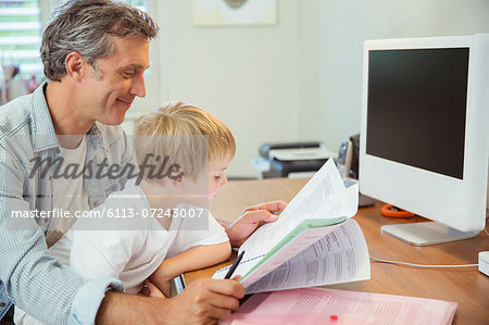 Father and son working in home office Stock Photo - Premium Royalty-Free, Image code: 6113-07243007