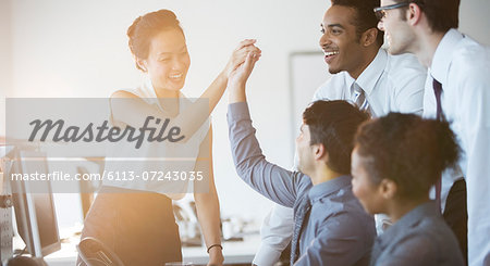 Business people cheering in office Stock Photo - Premium Royalty-Free, Image code: 6113-07243035