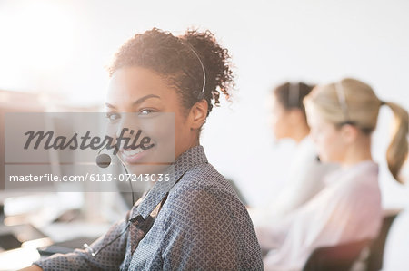 Businesswoman wearing headset in office Stock Photo - Premium Royalty-Free, Image code: 6113-07243036