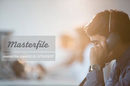 Businessman talking on telephone in office Stock Photo - Premium Royalty-Free, Image code: 6113-07243037
