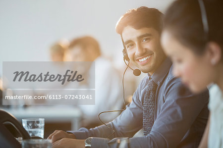 Businessman wearing headset in office Stock Photo - Premium Royalty-Free, Image code: 6113-07243041