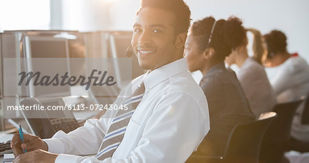 Businessman with headset smiling in office Stock Photo - Premium Royalty-Free, Image code: 6113-07243045