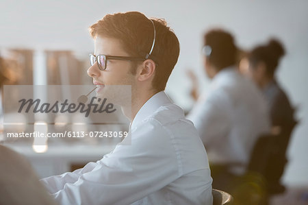 Businessman wearing headset in office Stock Photo - Premium Royalty-Free, Image code: 6113-07243059