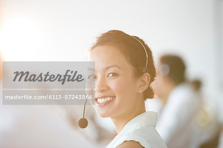 Businesswoman wearing headset in office Stock Photo - Premium Royalty-Free, Image code: 6113-07243066