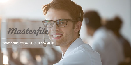 Businessman wearing headset in office Stock Photo - Premium Royalty-Free, Image code: 6113-07243070