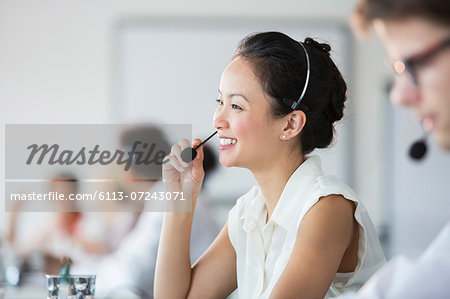 Businesswoman wearing headset in office Stock Photo - Premium Royalty-Free, Image code: 6113-07243071