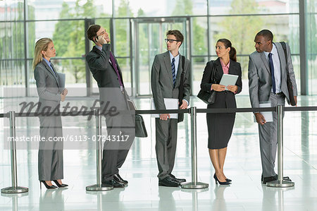 Businessman talking on cell phone in line Stock Photo - Premium Royalty-Free, Image code: 6113-07243117