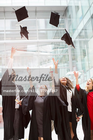 Graduates tossing caps in air Stock Photo - Premium Royalty-Free, Image code: 6113-07243267
