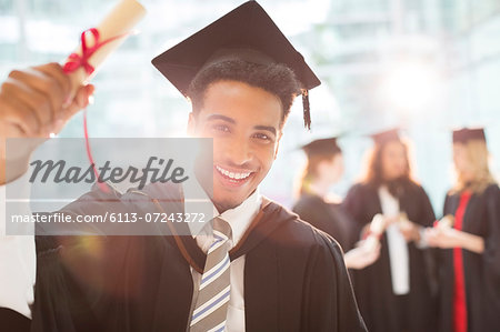 Smiling graduate holding diploma Stock Photo - Premium Royalty-Free, Image code: 6113-07243272