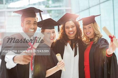 Graduates smiling with diploma Stock Photo - Premium Royalty-Free, Image code: 6113-07243289