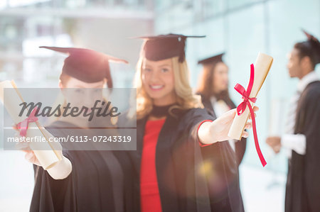 Smiling graduates holding diplomas Stock Photo - Premium Royalty-Free, Image code: 6113-07243319