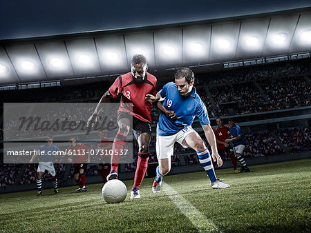 Soccer players chasing ball on field Stock Photo - Premium Royalty-Free, Image code: 6113-07310537