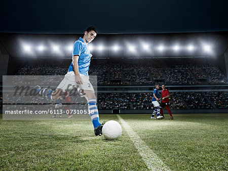 Soccer player kicking ball on field Stock Photo - Premium Royalty-Free, Image code: 6113-07310538