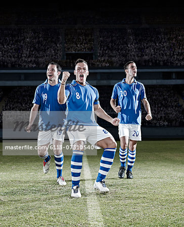Soccer players cheering on field Stock Photo - Premium Royalty-Free, Image code: 6113-07310540