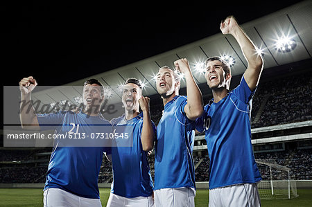 Soccer team cheering on field Stock Photo - Premium Royalty-Free, Image code: 6113-07310545