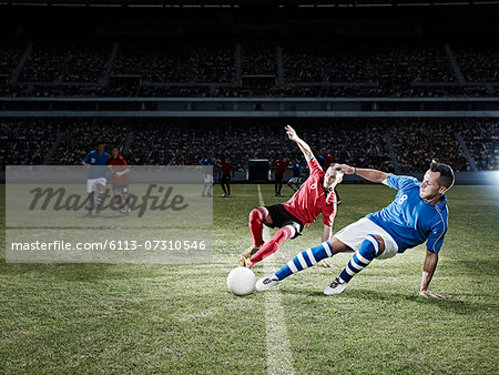 Soccer players kicking for ball on field Stock Photo - Premium Royalty-Free, Image code: 6113-07310546