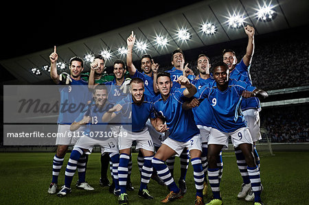 Soccer team cheering on field Stock Photo - Premium Royalty-Free, Image code: 6113-07310549