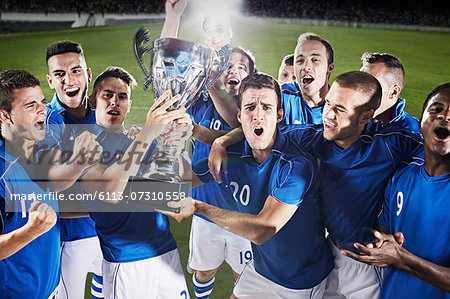 Soccer team cheering with trophy on field Stock Photo - Premium Royalty-Free, Image code: 6113-07310558