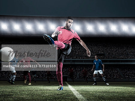 Soccer player kicking ball on field Stock Photo - Premium Royalty-Free, Image code: 6113-07310559